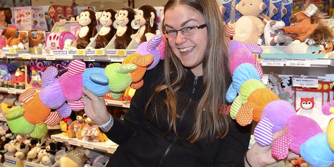 Kvinne i leketøysbutikk som holder leker