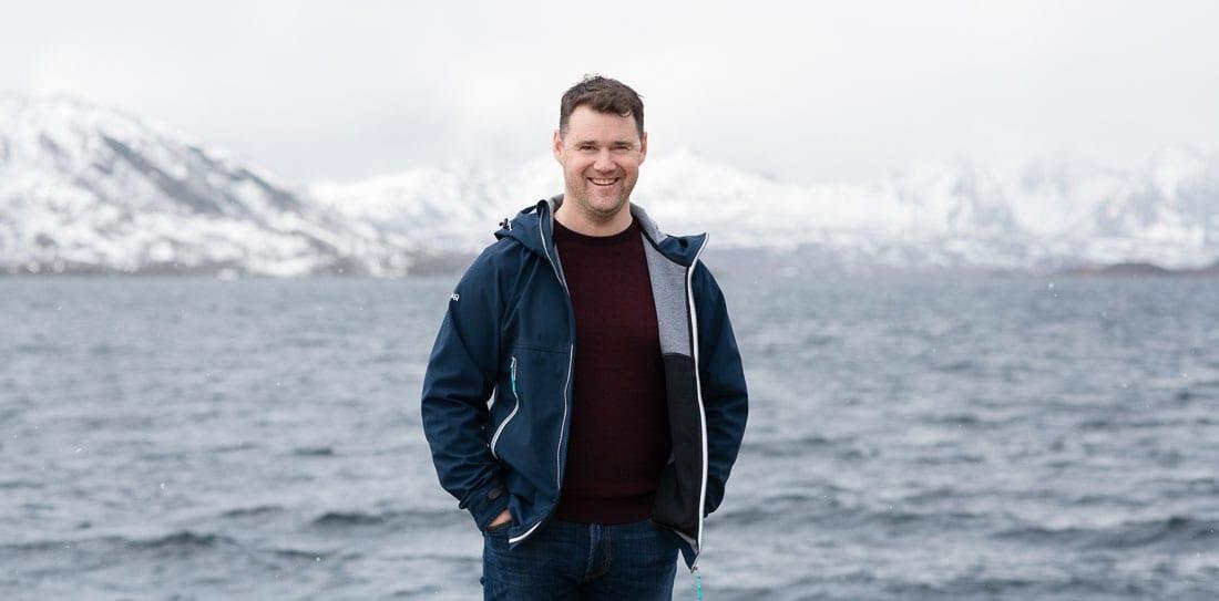 person smiler, med hav og fjell i bagrunnen